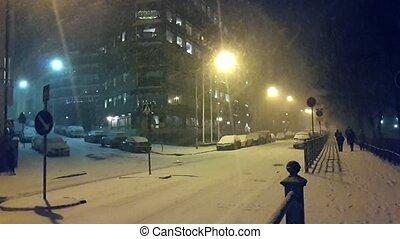 Snowfall at the city at night