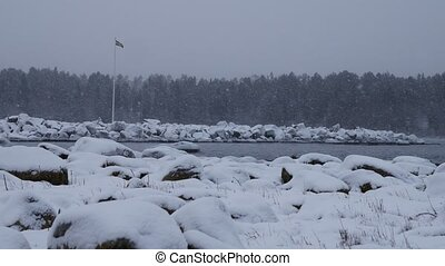 Snowfall in baltic sea, shot with sweden flag