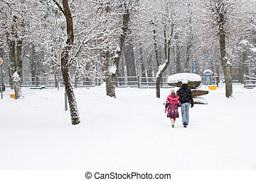 snowfall in city park, two people walking
