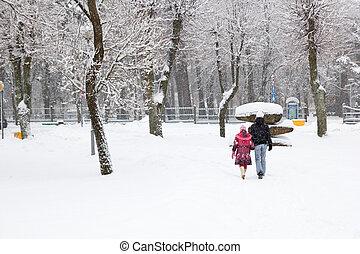 snowfall in city park, two people walking