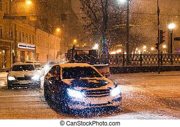 snowfall in night city - cars traffic under snow