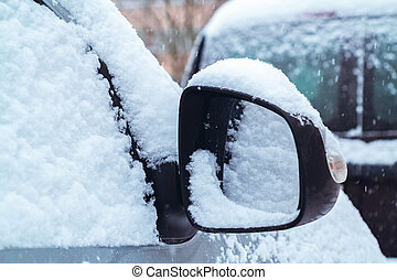 Snowfall in the city, part of the car covered by snow