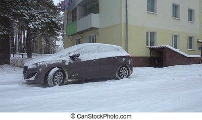 Snowfall in the city, snow covered car neer house.