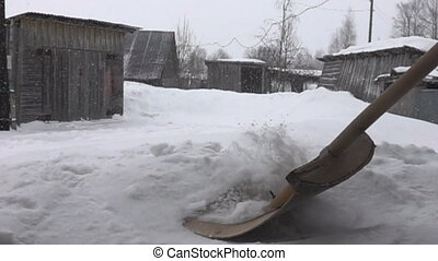 Snowfall in village and snow removal with wooden shovel -...