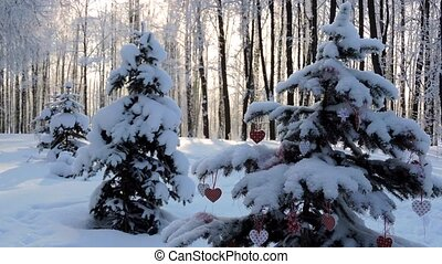 Snowfall in winter, branch with a Christmas heart sways in the wind