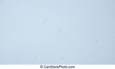 Snowfall on the background of bright sky