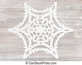 snowflake carved from paper on light brown surface