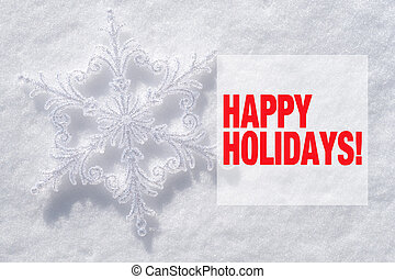 Snowflake christmas decoration and Happy holidays text on snow background
