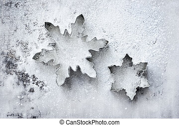 Snowflake cookie cutters on a powdered baking sheet