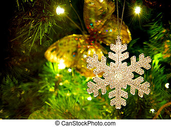 Snowflake ornament hanging from a Christmas tree.