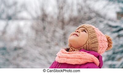 Snowflakes fall on the face of a little girl. She stands and looks to the sky.