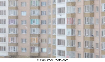 Snowflakes falling, winter window view. Apartment building. Blurred background