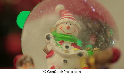Snowglobe with snowman on the Christmas trees