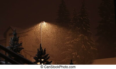 Snowing at night on the background of a lamppost. - Snowfall...