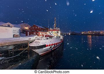 Snowing in Ballstad village at twilight in winter season, Lofoten islands, Norway
