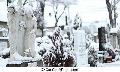 Snowing on Cemetery. - Grave stone sculpture in the...