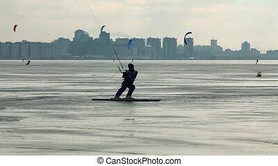 Snowkiter tracking shot - Snowkiter in motion on frozen ice