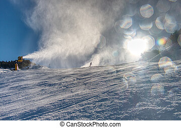 Snowmaking spraying snow on the piste for mountain skiers