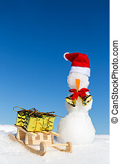 snowman and a sledge with gifts in the snow