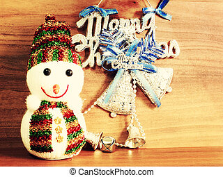 snowman and merry christmas decoration on wooden background with filter effect retro vintage style