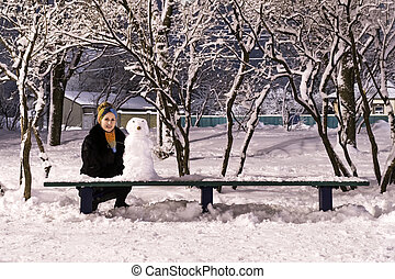 Snowman and woman at night park
