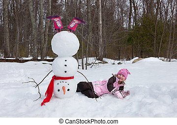 4-5 years old girl lying down next to a snowman