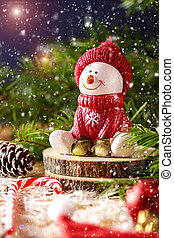 Snowman in a red cap with the branches of fir