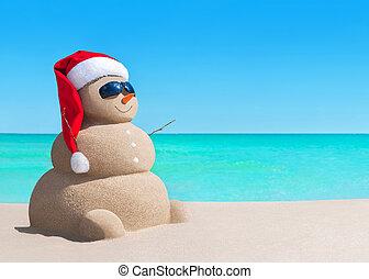 Snowman in Christmas Santa hat and sunglasses at sea beach -...