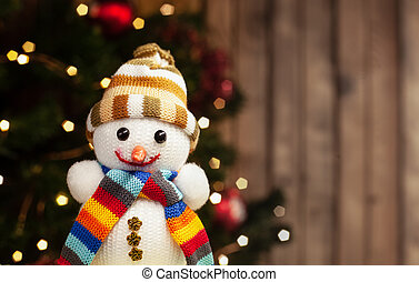 Snowman in hat and scarf Christmas toy on the background of a Christmas tree with a garland and a wooden wall