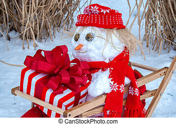 snowman in sled with holiday gift