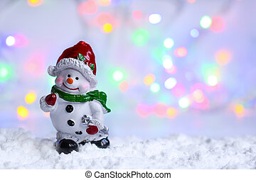 Snowman in the snow with bokeh blurred light.
