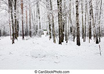 Snowman in winter forest