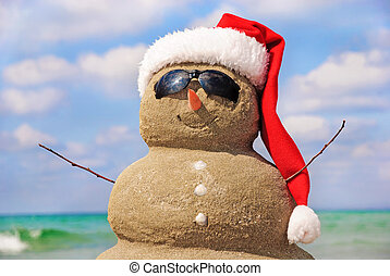Snowman made out of sand against the sky. Christmas concept.