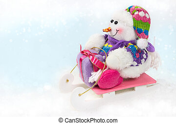 Snowman on a sled with a Christmas gift