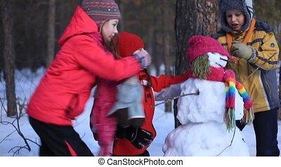 Snowman - Three little children making a snowman in winter...