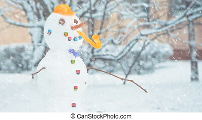 snowman under falling snow - funky snowman at winter season...