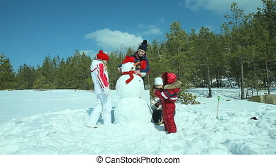 Snowman under winter sun - Happy family of four busy doing a...