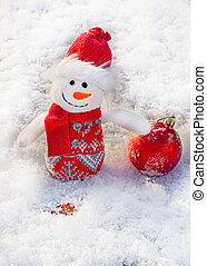 Snowman with a red ball on a background of white snow. Christmas and New Year concept