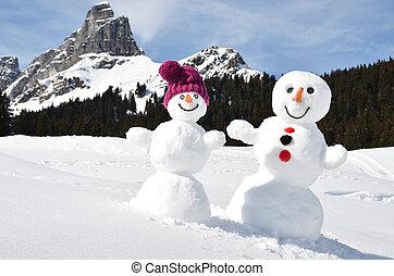 Snowmen against Alpine panorama