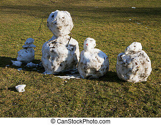 snowmen made with snowballs and decorated by twigs on a...