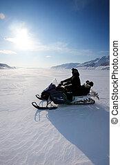 Snowmobile - A snowmobile on frozen ice on a barren winter...