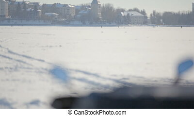 Snowmobile on the frozen lake. View of the instrument panel of a snowmobile in the background of a winter city.