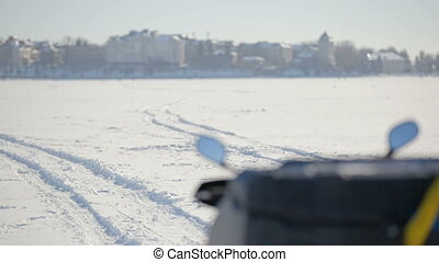 Snowmobile on the frozen lake. View of the instrument panel of a snowmobile with the flag of Ukraine in the background of a winter city.