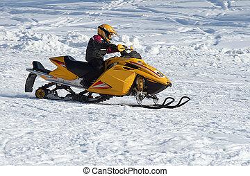 A snowmobilier takes a sharp turn through powdery snow.