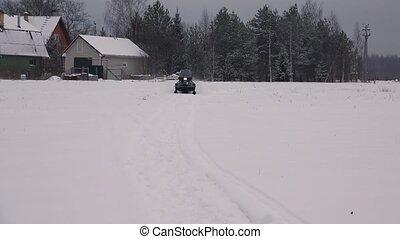 Snowmobile rides on winter field. 4K.