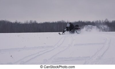 Snowmobile rides on winter field. 4K.