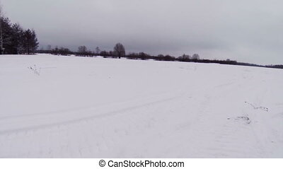 Snowmobile rides on winter field.