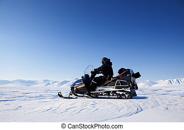 A snowmobile on a frozen lake against a winter landscape with mountains