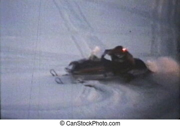 Two snowmobiles do some spins on a frozen river while out having fun snowmobiling. (Scan from archival 8mm film)