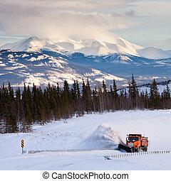 Snowplow clearing road in scenic Yukon T Canada
